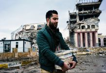 Man carrying books in front of war-damaged buildings (© Dimitar Dilkoff/AFP/Getty)