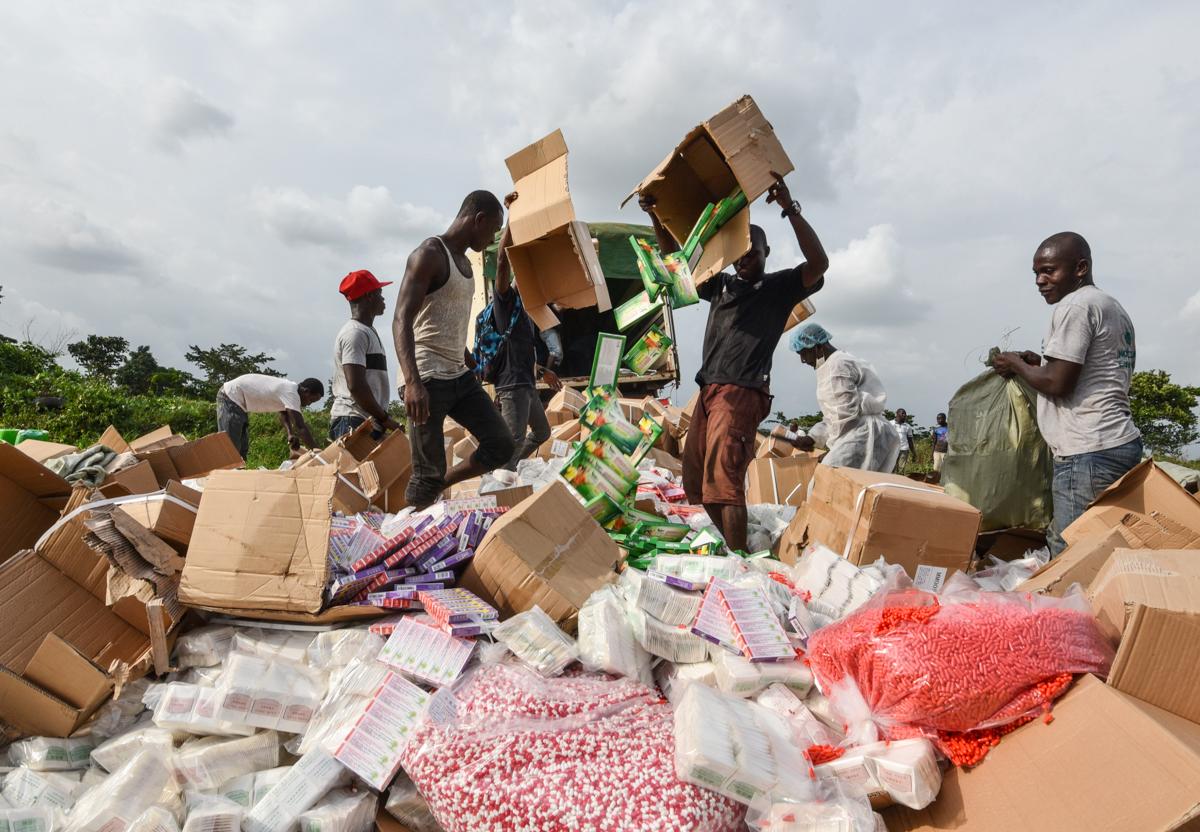 Gente tirando cajas de píldoras a una pira. (© Sia Kambou/AFP/Getty)