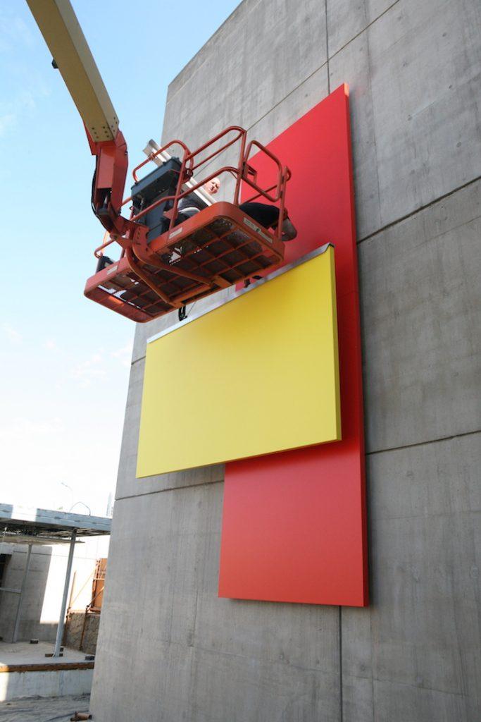 Hombre en una grúa instalando una enorme obra de arte (Foto cedida por FAPE)