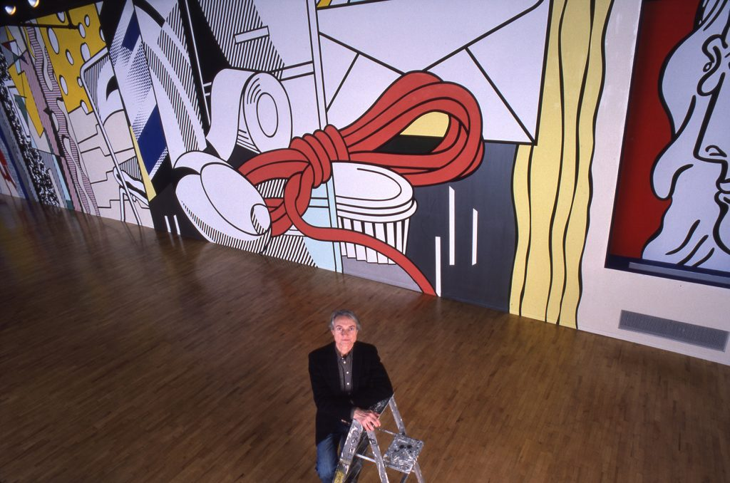 Man on a ladder looking up, colorful mural behind (© Estate of Roy Lichtenstein. Photo © Michael Abramson)