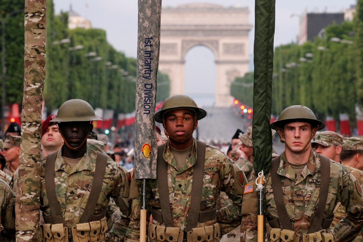 Soldiers in uniform standing on the Champs-Élysées with the Arc de Triomphe behind them (© Pascal Rossignol/Reuters)