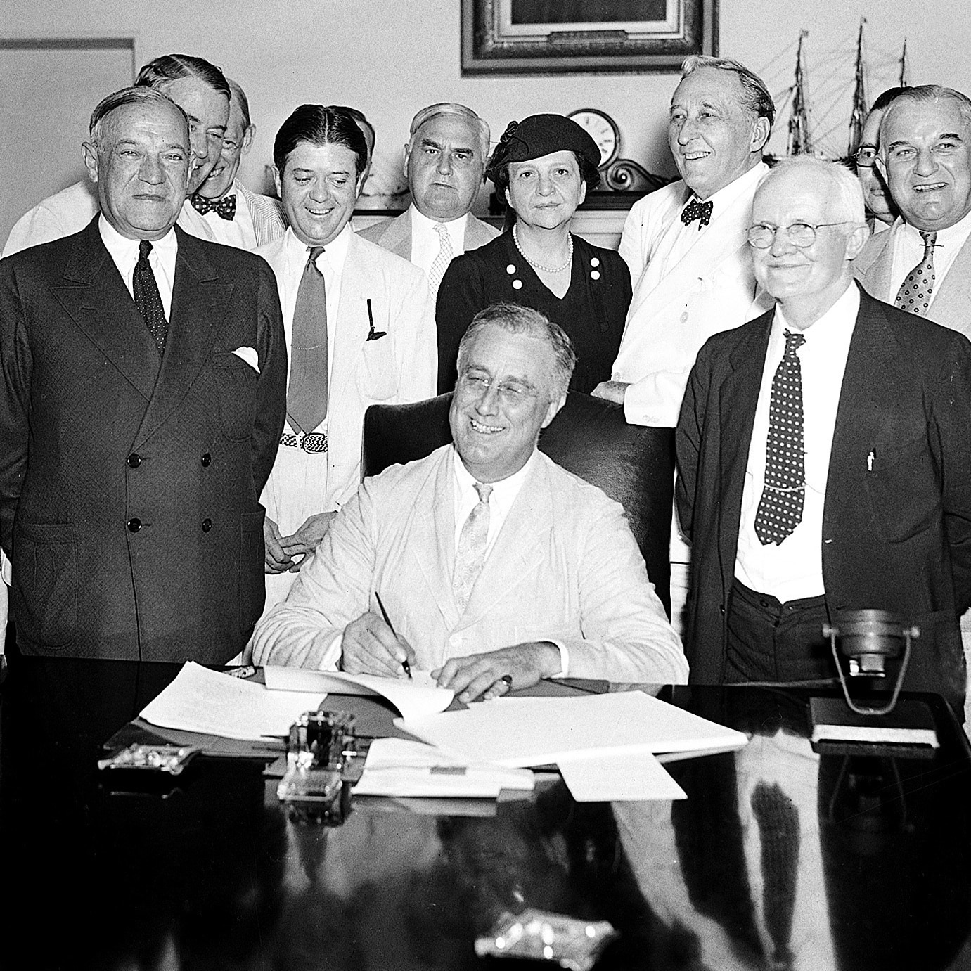 Franklin D. Roosevelt signing document while while men and a woman stand behind him (© AP Images)