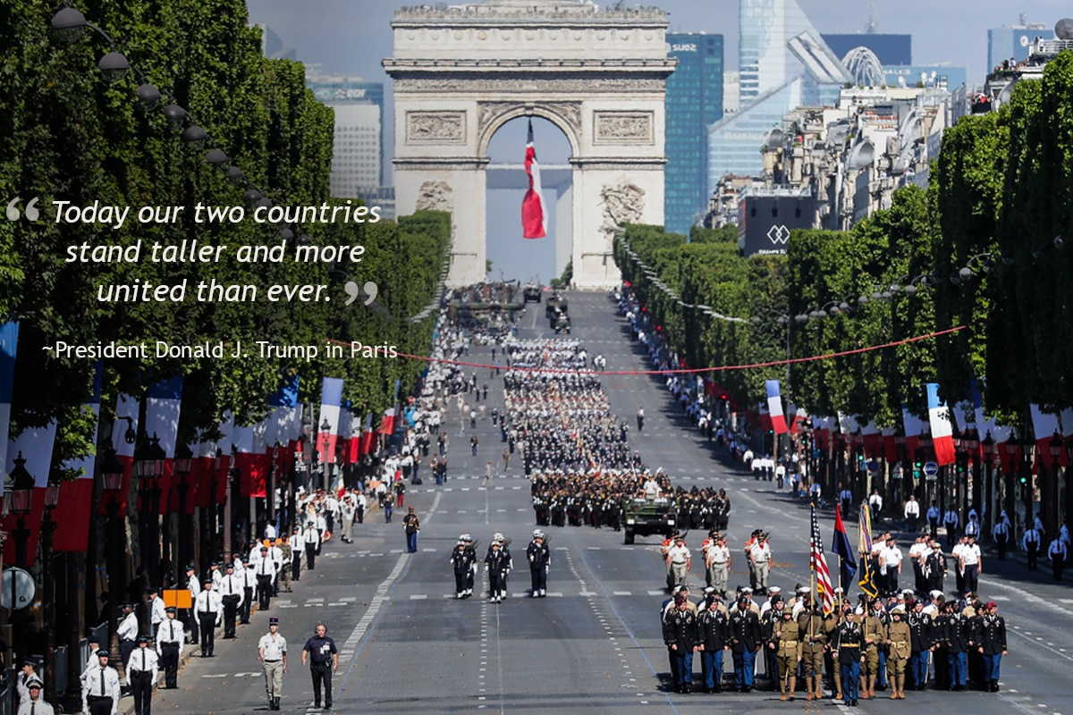 Troops marching down street in formation with L'Arc de Triomphe in background (© AP Images)