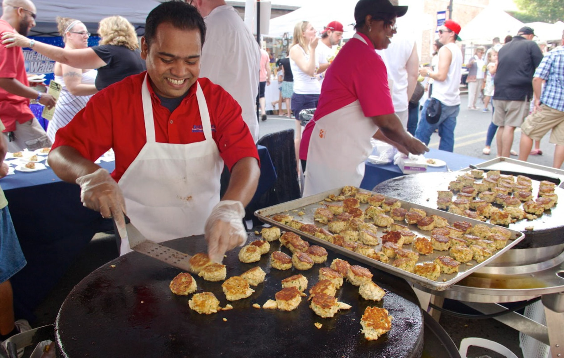 Man preparing crab cakes on large griddle (Cambridge Main Street)