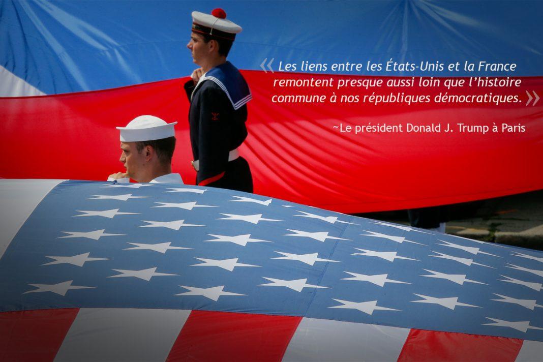 Deux marins, l'un américain et l'autre français, debout à côté d'un grand drapeau de leur pays (© AP Images)
