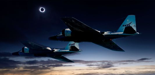 Dos aviones vuelan en cielo oscuro (NASA)