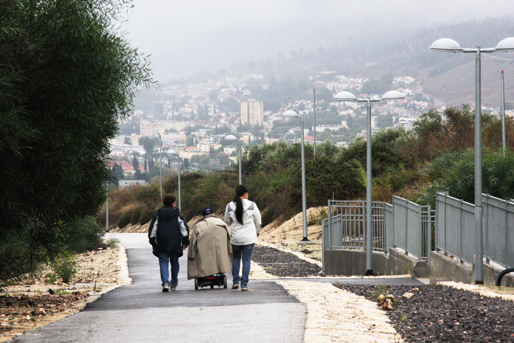 Personas caminando en un sendero con vista de una ciudad al fondo (© Shmuel Bar-Am)