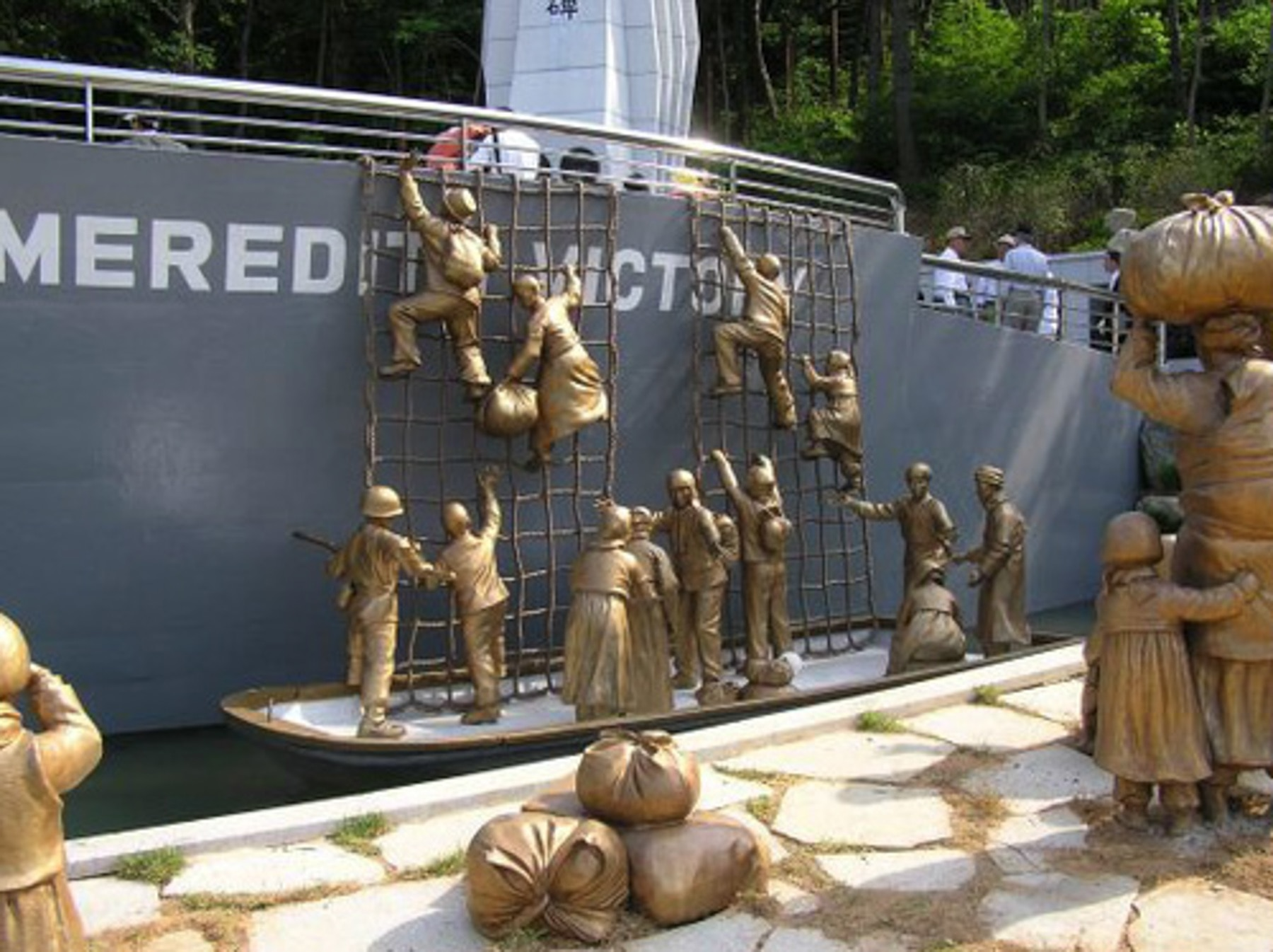 Monument depicting soldiers helping people climb onto a ship (U.S. Navy)