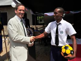 Mark Green shaking hands with man holding soccer ball (U.S. Navy)