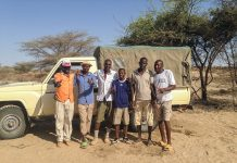 Group of men standing by truck in dry landscape (© Isaiah Nengo)