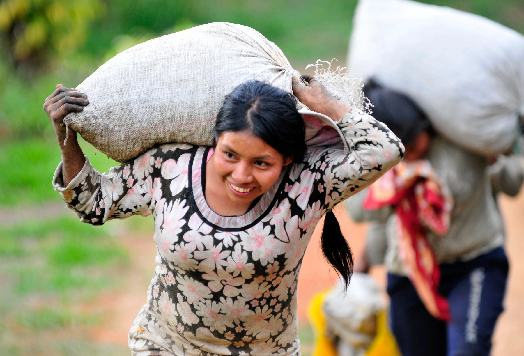 Woman carrying bag of coffee on her back (Neil Palmer/CIAT)