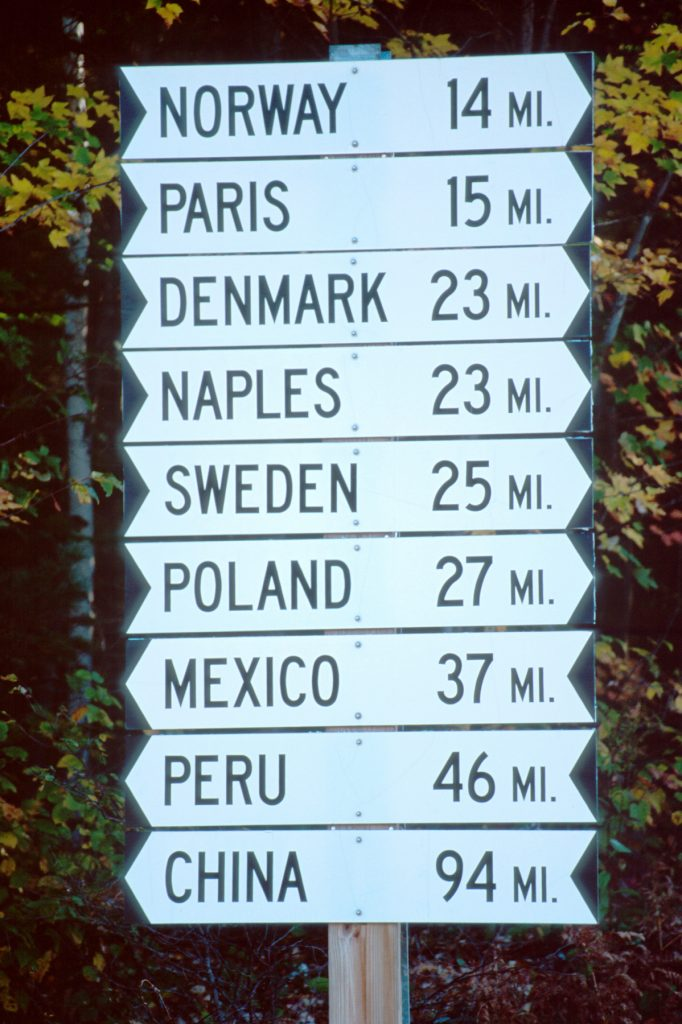 Road sign with distances for Norway, Paris, Denmark, Naples, Sweden, Poland, Mexico, Peru and China (© Alamy)