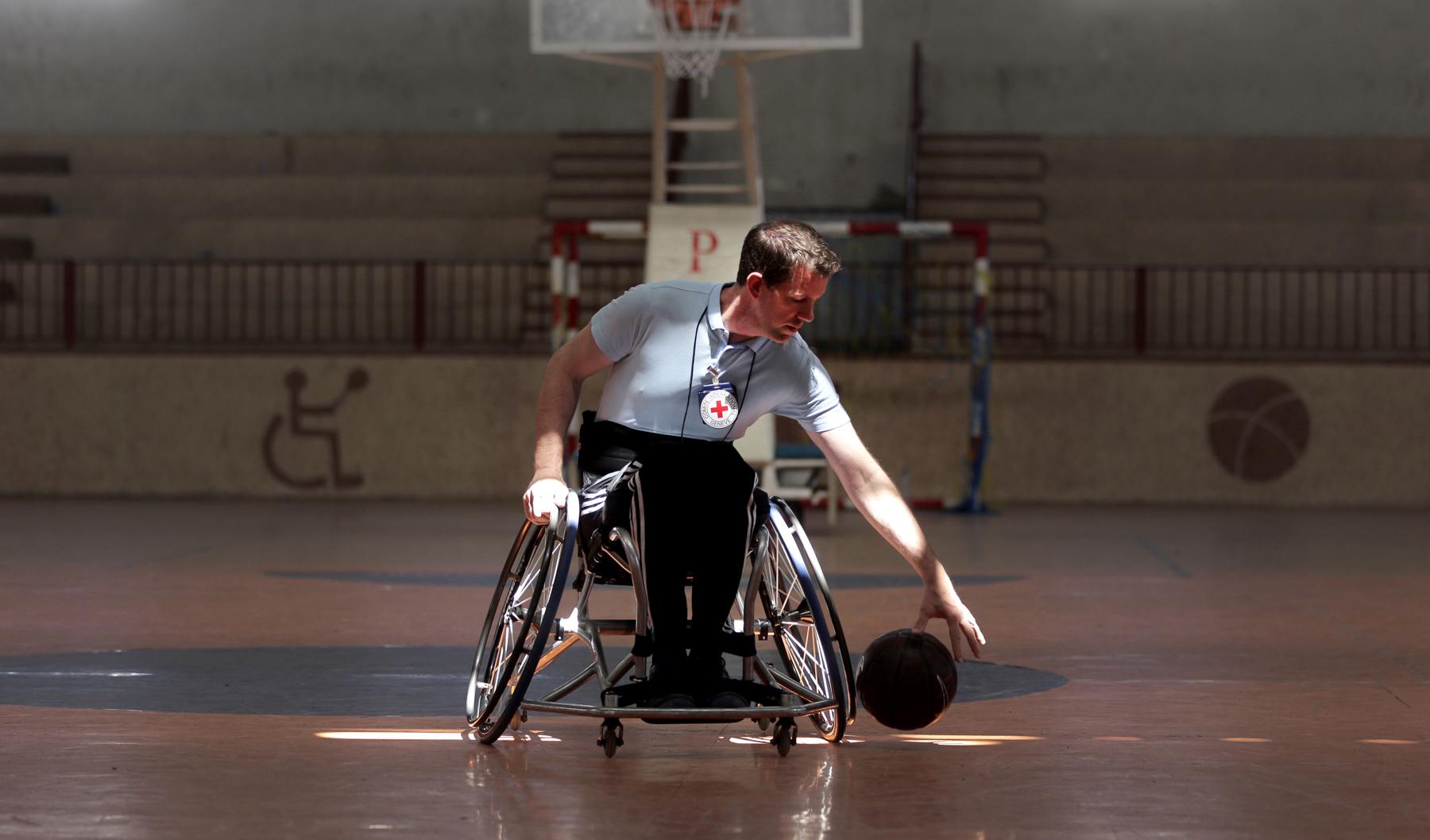 Un homme en fauteuil roulant, sur un terrain de basket, en train de faire rebondir un ballon (© AP Images)