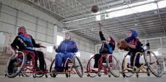 Mulheres em cadeiras de rodas jogando basquete (© AP Images)