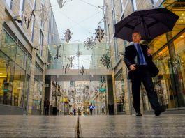 Man with umbrella walking through outdoor shopping center (© AP Images)