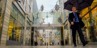 Man with umbrella walking through outdoor shopping center (© AP Images)