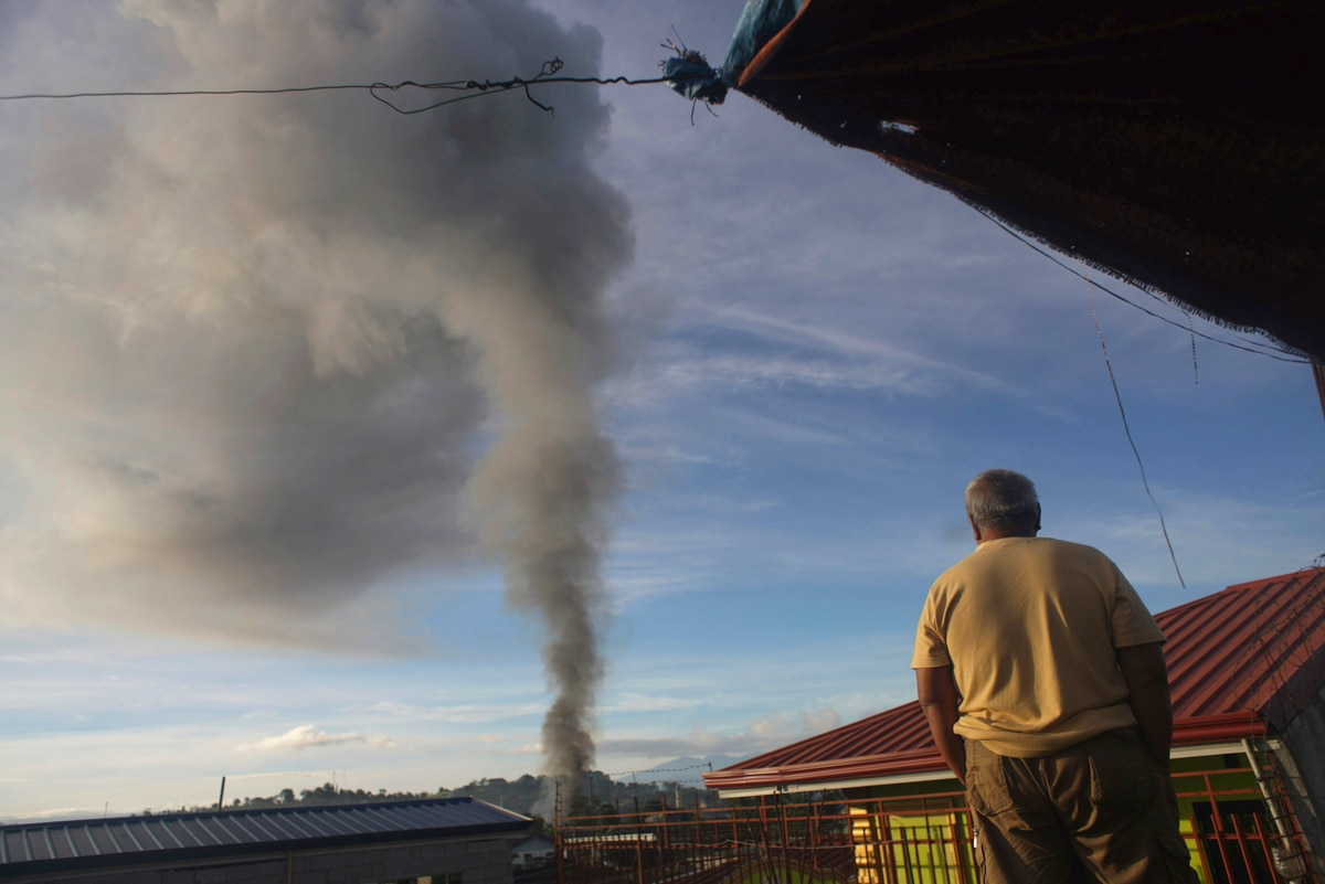 Man looking at billowing smoke in distance (© AP Images)