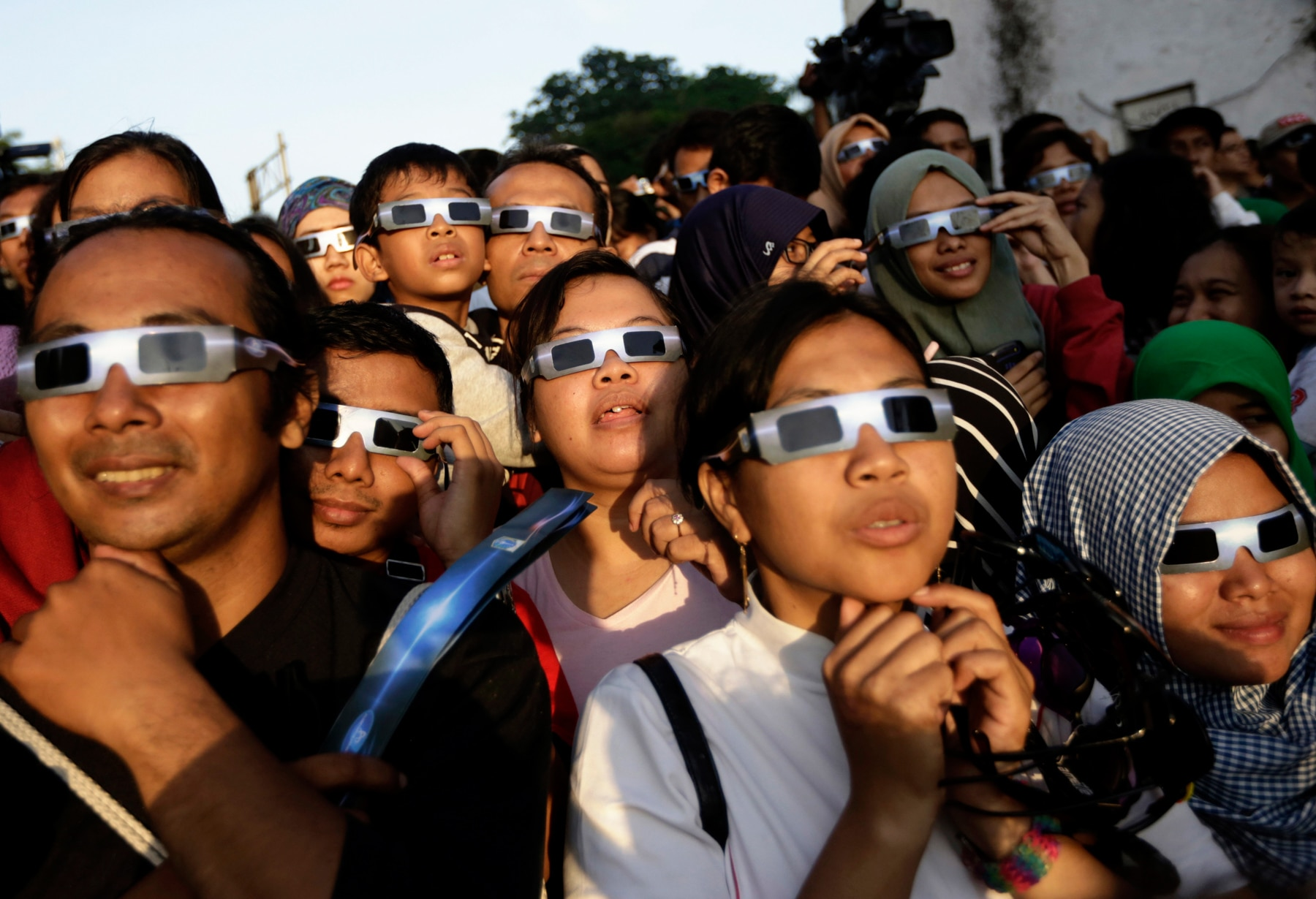 Group of people wearing glasses with dark lenses and frames covering the sides of their eyes (© AP Images)