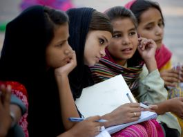 Four Pakistani girls listening to a teacher (© AP Images)
