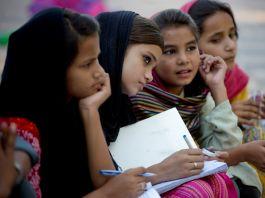أربع فتيات باكستانيات يستمعن إلى مدرستهن. (© AP Images)