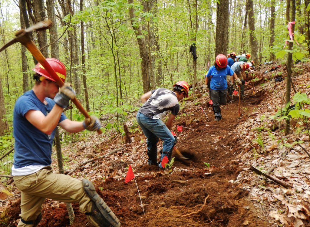 Workers with pick axes and shovels dig along a path (Appalachian Trail Conservancy)