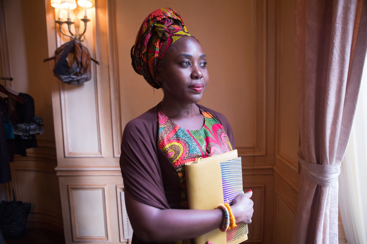 Woman holding folder and wearing bright African clothing (State Dept./D.A. Peterson)