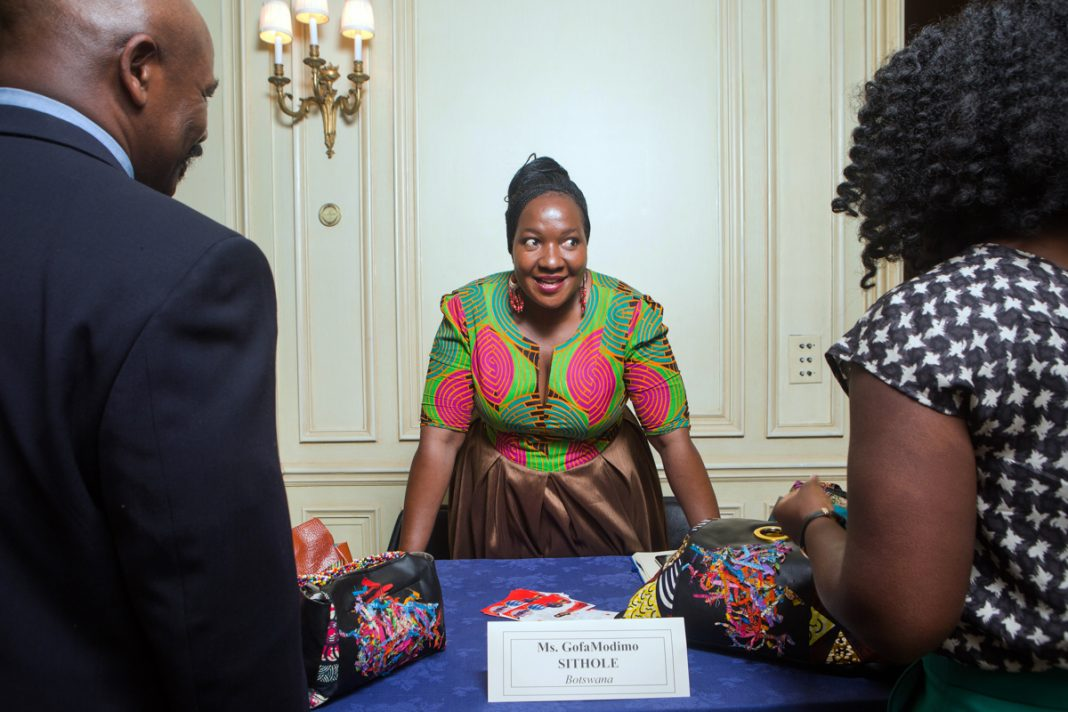 Woman leaning over table flanked by two people (D.A. Peterson/Dept. of State)