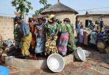 Des Africaines pieds nus dans un petit bassin contenant des noix (Alaffia)