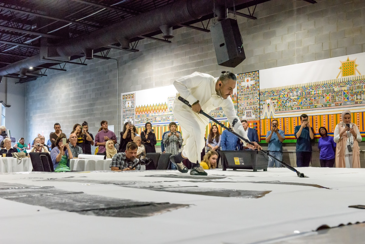 Man pushing paint across large canvas on raised platform as people look on (© Doug Coombe/Arab American National Museum)