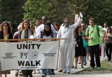 "People walking down sidewalk, carrying sign saying ""Unity Walk"" (© Washington Post via Getty Image)"
