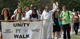 """Personas caminan por una acera con una pancarta que dice """"Caminata por la Unidad"""" (© Washington Post vía Getty Image)"""