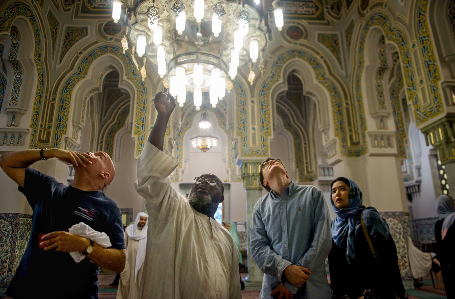 أشخاص يتطلعون لأعلى إلى كتابات على الحائط في المسجد. (© Amanda Voisard for The Washington Post via Getty Images)