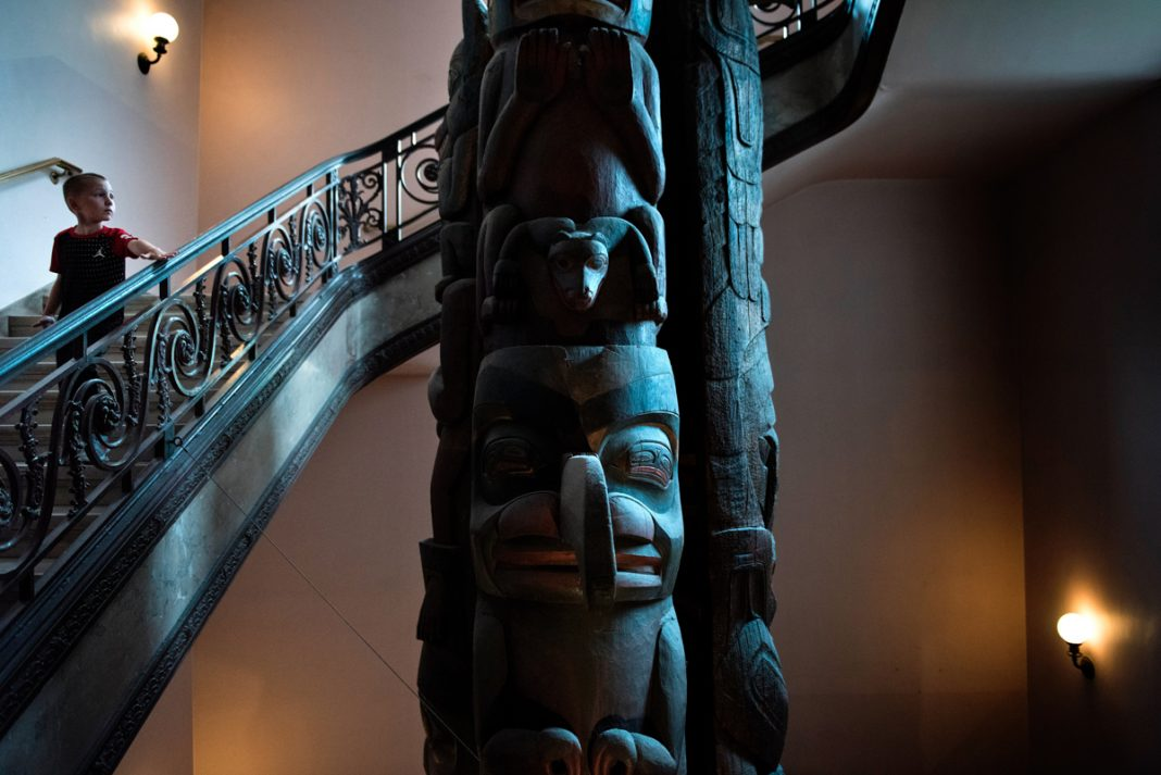 Boy on staircase looking at giant totem pole (© Brendan Smialowski/AFP/Getty Images)