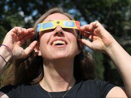 زنی در حال لبخند از عینک کسوف استفاده می کند. (عکس از بوستون گلوب/ عکس های گتی)
