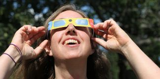 Smiling woman wearing eclipse glasses (© Boston Globe via Getty Images)