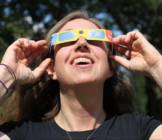 Mujer sonriente con gafas protectoras para ver el eclipse (© Boston Globe vía Getty Images)