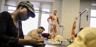 Young woman writing in classroom with model skulls and human body (© Ricky Carioti/Washington Post/Getty Images)