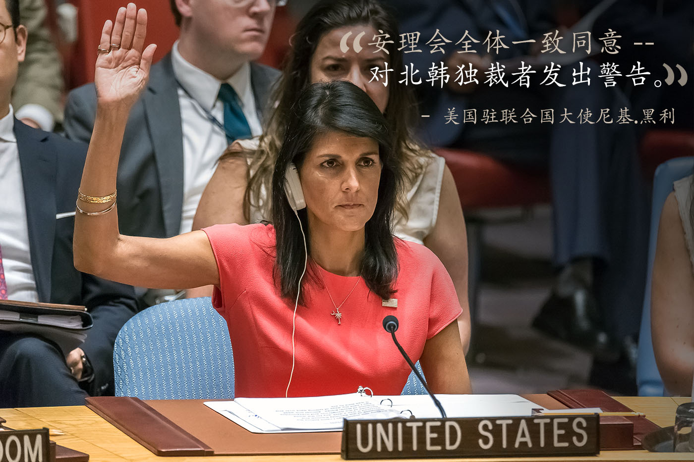 U.S. Ambassador to the U.N. Nikki Haley seated at table with hand raised, with quote (© Getty Images)