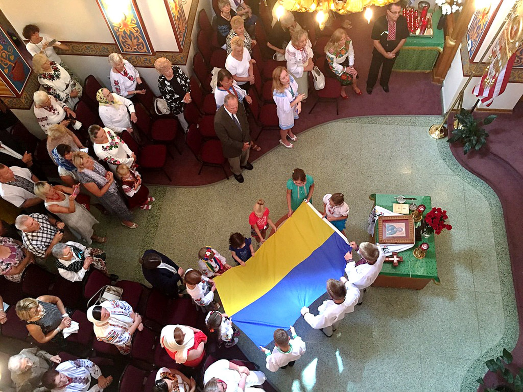 Parishoners carrying Ukrainian flag into a church (Ukrainian Orthodox Church of the USA)
