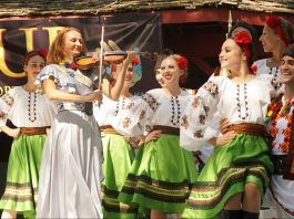 Woman playing the violin with dancers in Ukrainian dress behind her (Christine Syzonenko)