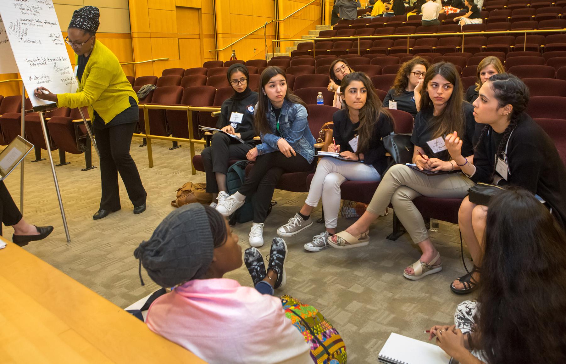 Mujer escribiendo notas en un cartel apoyado en un caballete mientras un grupo atiende a otra mujer (Depto. de Estado/D.A. Peterson)