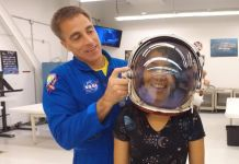 Astronaut placing helmet on teenage girl's head (Globo)
