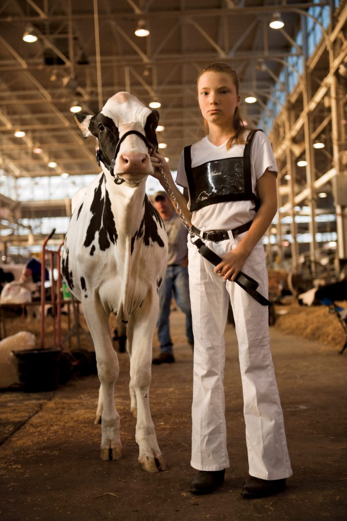 Jeune fille debout à côté d'un veau (© Joel Sartore/National Geographic)