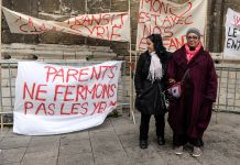 Two women standing in front of hand-painted protest signs ( (© Laurent Dubrule /Reuters)