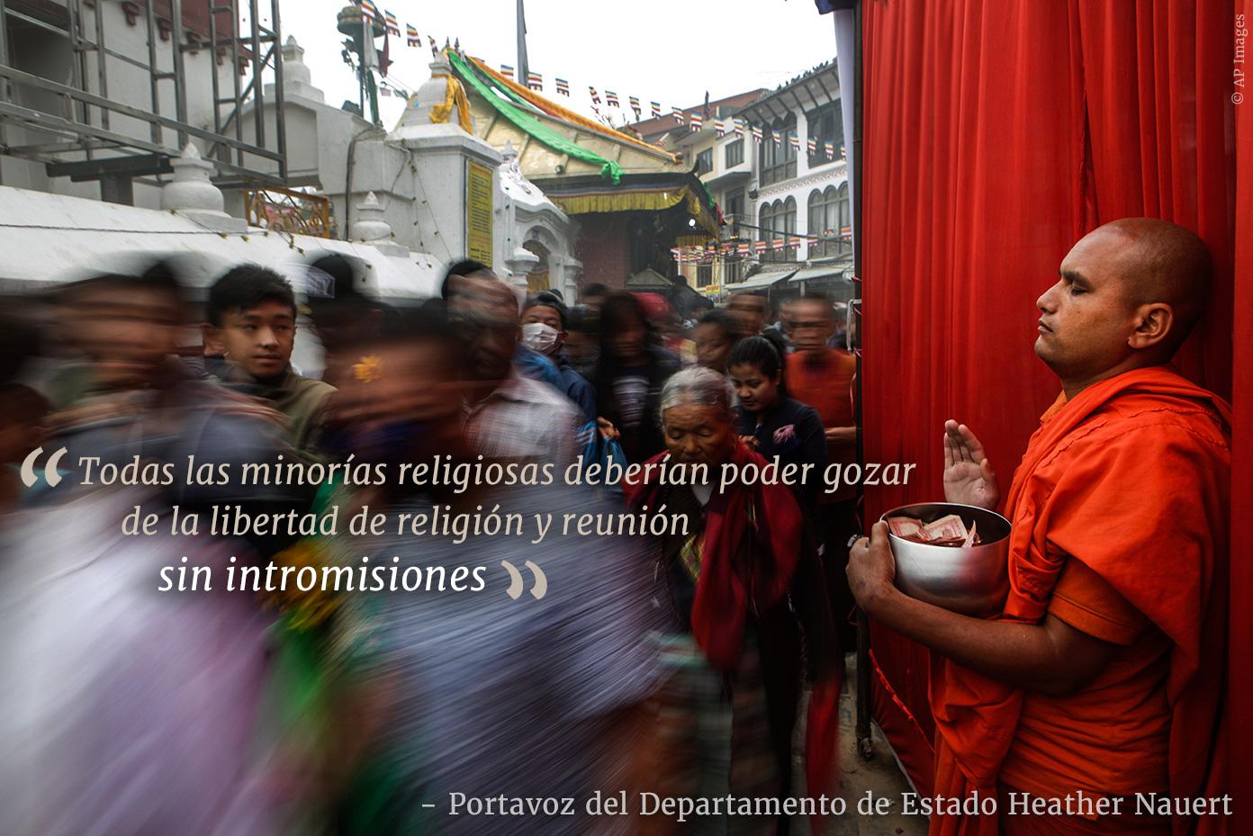 Monje budista pide a personas que pasan (© AP Images)
