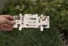 Hand holding Foldscope, with plants and grass in background (State Dept.)