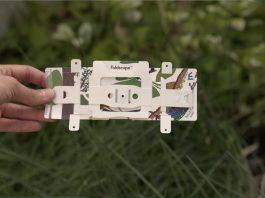 Mão segura o Foldscope, com plantas e grama em segundo plano (Depto. de Estado)