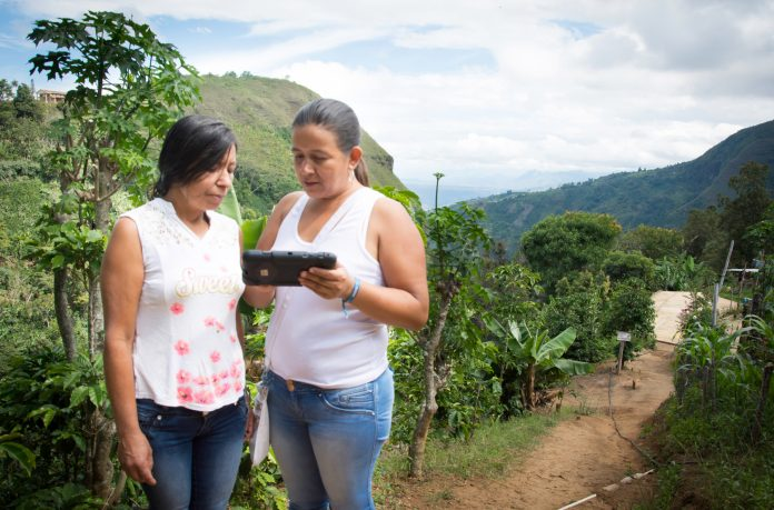 Two women standing on dirt path and looking at tablet (Fundación Capital)