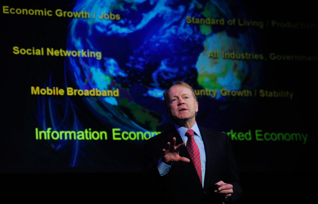John Chambers in front of large projector screen with phrases and picture of globe (© AP Images)