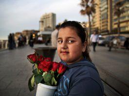 Girl holding flowerpot on city street (© AP Images)